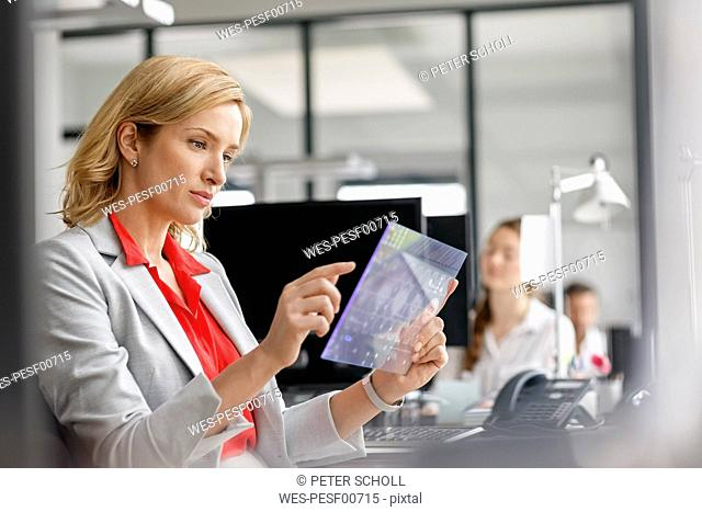 Businesswoman at desk in office using futuristic tablet