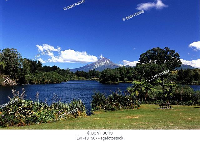 View over landscape and lake, volcano Mt. Taranaki in the distance, North Island, New Zealand