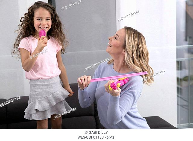 Mother and little daughter playing together with toy violin