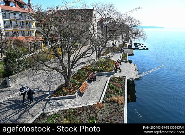 03 April 2020, Baden-Wuerttemberg, Ìberlingen Am Bodensee: Only a few people stay on the promenade right next to Lake Constance