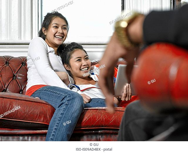 Three friends chatting in living room