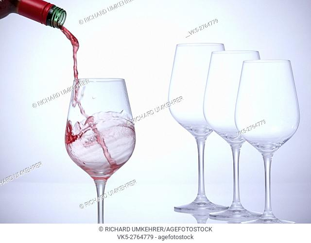 Motion picture of a man hand fill a glass with wine. Three empty glasses stand in a row. . Against a white background and a vignette
