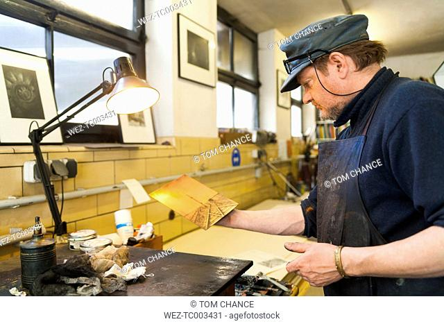 Germany, Bavaria, Mature man looking at copperplate in print shop