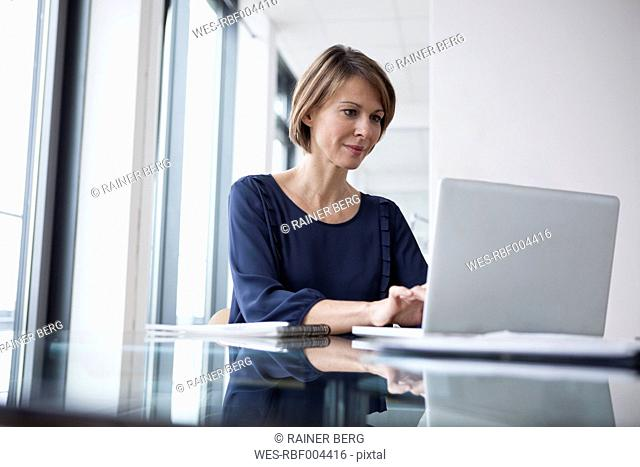 Businesswoman working on laptop at office desk