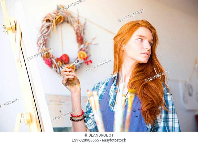 Cute lovely young woman painter with long red hair working in art workshop