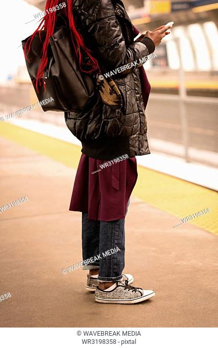 Woman using mobile phone at railway platform