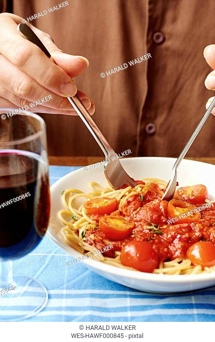 Man eating spaghetti with tomato sauce, close-up
