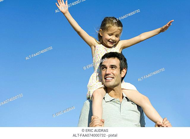 Father carrying daughter on his shoulders