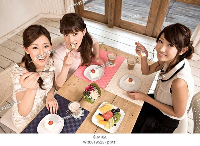 Three Young Women Enjoying Dessert