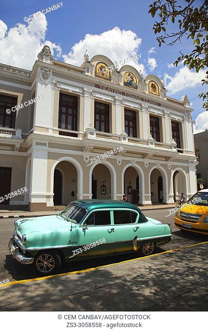 Old American car in front of the Tomas Terry Theatre at Jóse Martí Park, Plaza De Armas, Cienfuegos, Cuba, West Indies, Central America