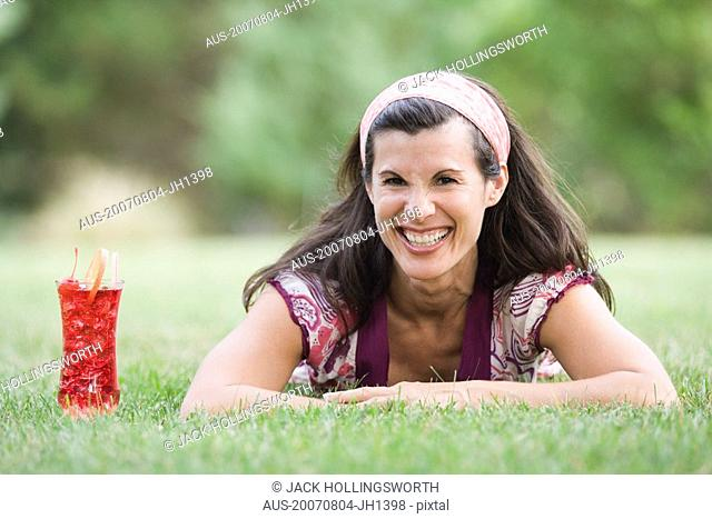 Portrait of a mature woman lying on grass with a glass of juice beside her