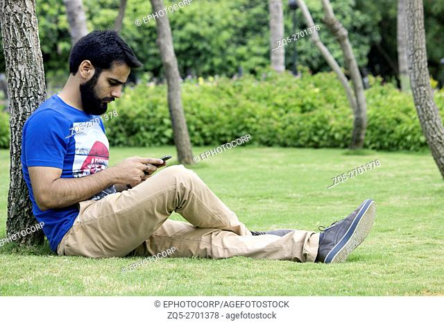 Young person using a mobile phone in leisure, Magarpatta city, Pune, Maharashtra, India