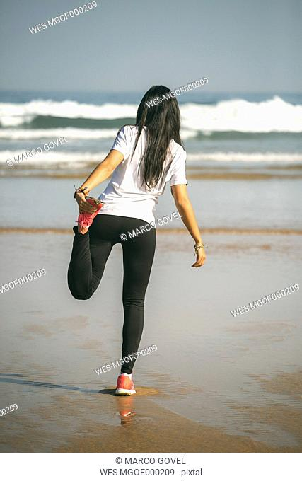 Spain, Gijon, young woman stretching on the beach