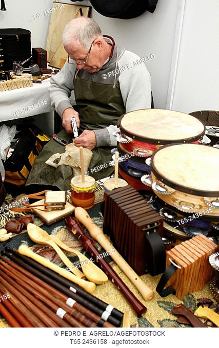 A craftsman of musical instruments with their products at a craft fair in Lugo