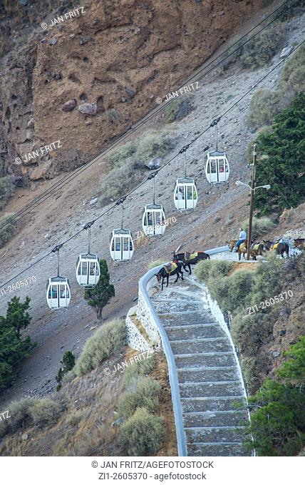 donkeys with tourists at stapes and cablecars at fyra at santorini in greece
