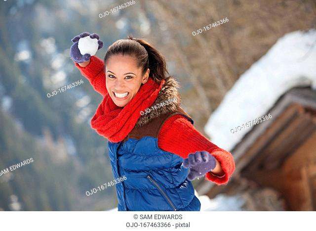 Portrait of smiling woman throwing snowball