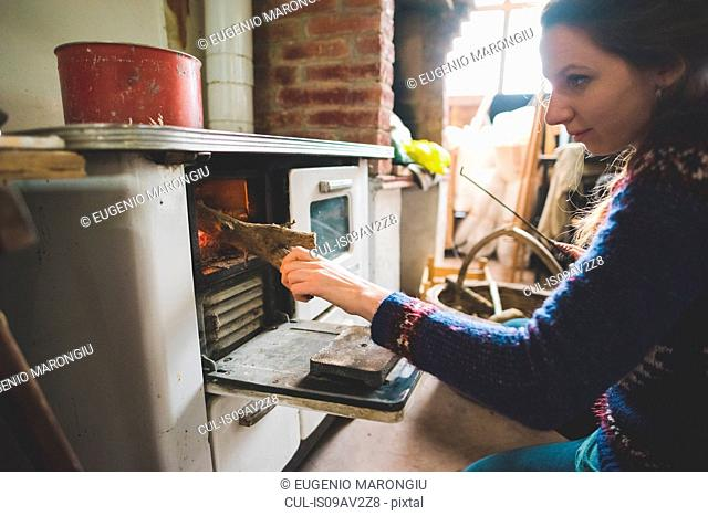 Side view of young woman putting firewood into wood burner
