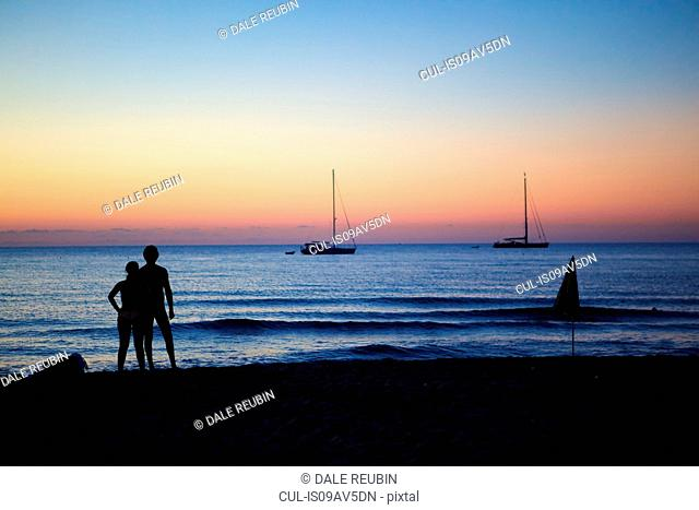Tourists looking at sea view at dusk, Cefalu, Sicily