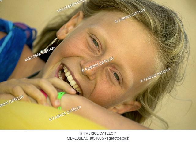 Portrait of a smiling little girl with a blue pareo on the beach