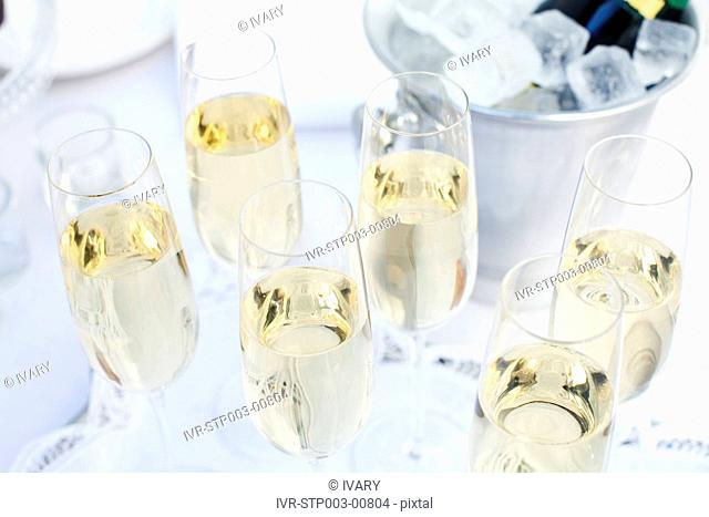 Close-up of glasses filled with white wine and bottle in ice bucket