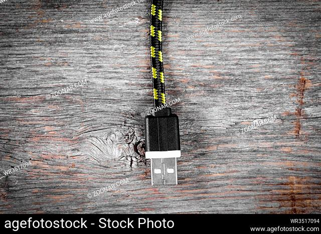 Nylon braided USB cable hanging over wooden background