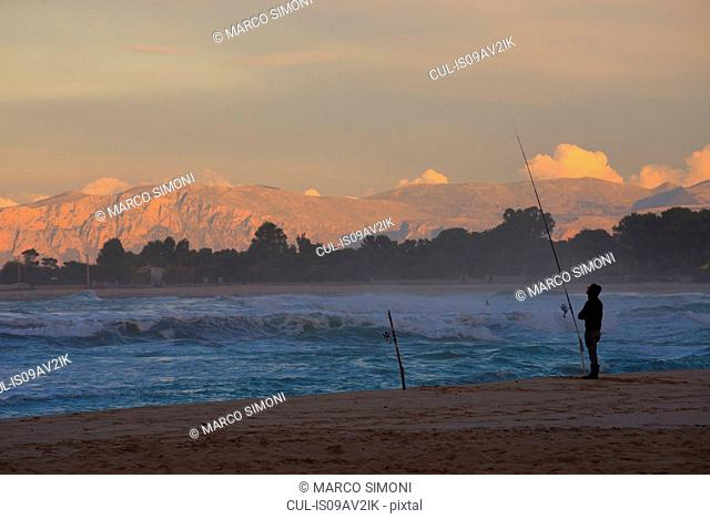 Silhouetted man fishing from beach at sunset, Macari, San Vito Lo Capo, Sicily, Italy