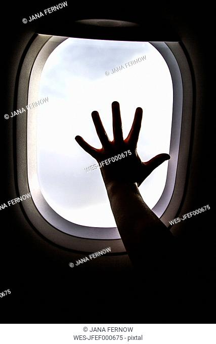 Silhouette of girl's hand on window on board of an airplane