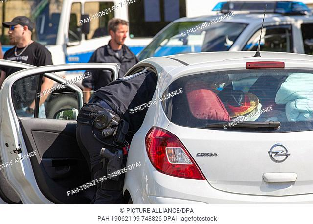 21 June 2019, Saxony, Ostritz: A policeman searches a visitor's car in the parking lot opposite the hotel where the so-called Shield and Sword Festival takes...
