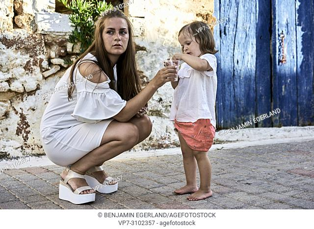 mother holding plastic cup to daughter, outdoors on street