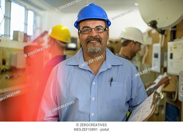 Smiling electrician instructor with students in background