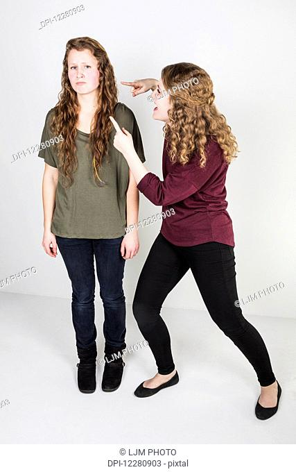Studio shot of one friend making fun of another friend; Alberta, Canada