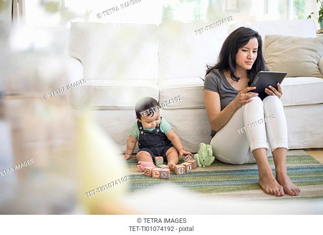 Mother using tablet pc while her son (6-11 months) playing with building blocks