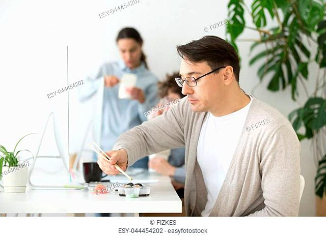 Middle aged male worker eating sushi at workplace while working at desktop computer, employee enjoying Japanese rolls spending lunch break at office desk