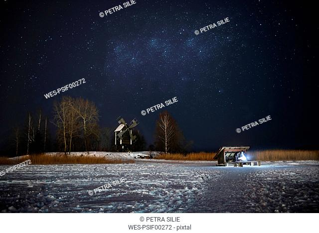 Finland, Kuopio, woman at campfire in winterat night