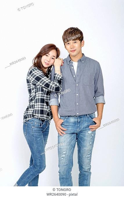 Young smiling couple in shirts and jeans posing