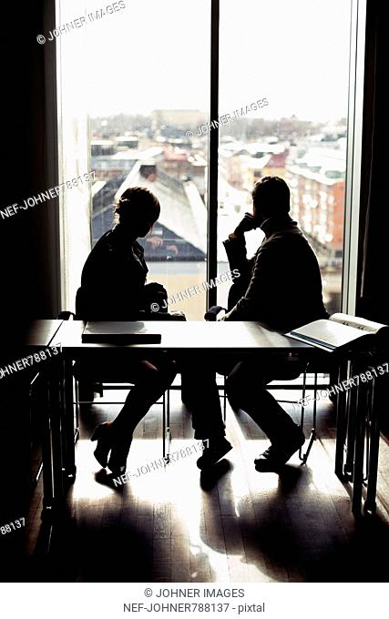 Two people in an office looking out of a window, Sweden