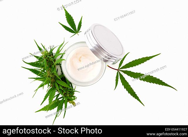 Cannabis hand cream in silver dose with marijuana plant, isolated on white background from above. Cannabis cosmetics