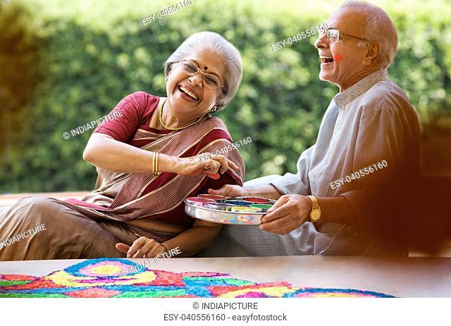 Old couple making a rangoli