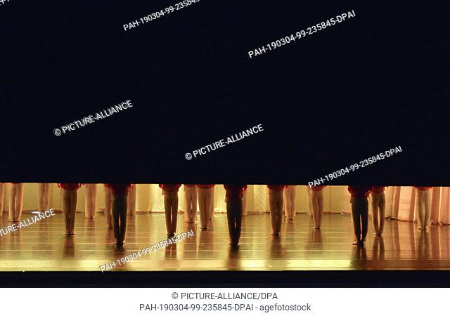 06 February 2019, Saxony, Leipzig: The curtain rises in the Leipzig Opera during rehearsal to form a ballet piece, feet and legs become visible