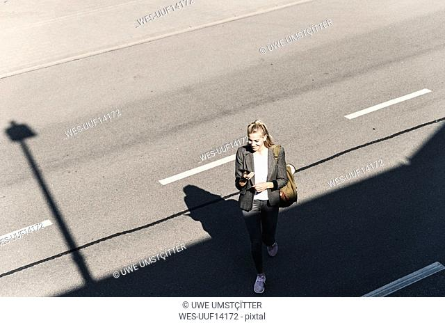 Young woman walking on empty road, talking into her smartphone