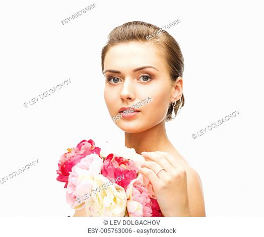 beauty and jewelry - woman wearing earrings and wedding ring with flowers