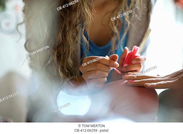 Woman painting friend's nails