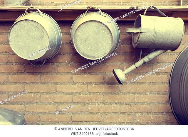 Metal Watering Cans by Brick Wall in garden wood shelf