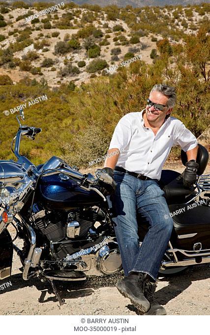 Senior man leans on motorcycle in desert