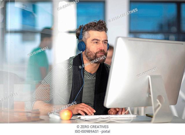 Man in office wearing headphones, using computer