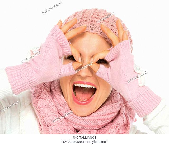 Happy young woman in knit winter clothes looking through glasses shaped hands