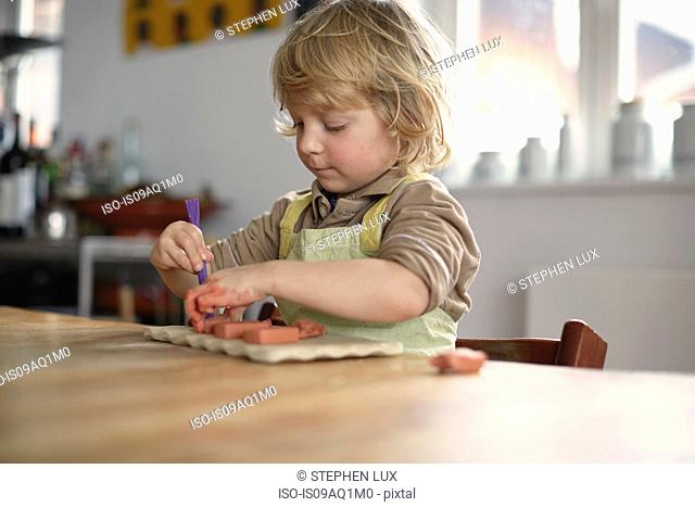 Young boy sitting at table using tool to model clay