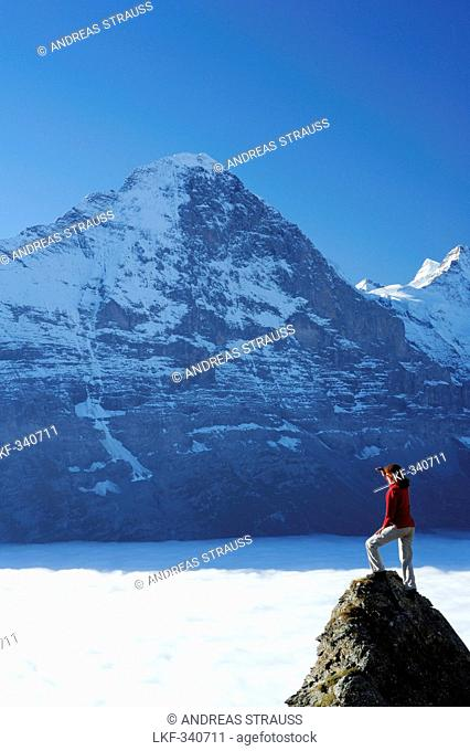 Woman standing on rock and looking towards north face of Eiger above sea of fog, Bussalp, Grindelwald, UNESCO World Heritage Site Swiss Alps Jungfrau - Aletsch