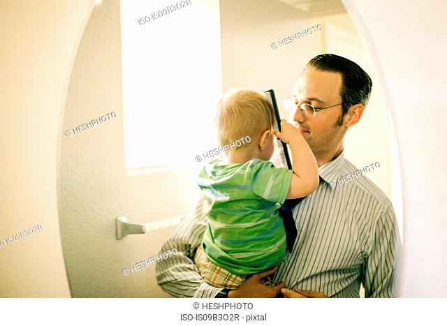 Father holding young son, son combing hair, reflected in mirror