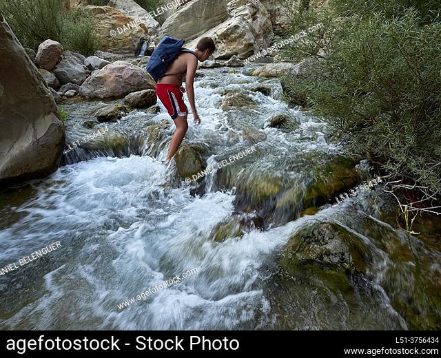 Boy walking through the Villahermosa river, Ludiente, Castellón, Spain
